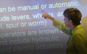 Faculty reviewing notes on a whiteboard