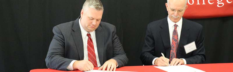 Cayuga President Brian Durant and Wells College President Jonathan Gibralter sign formal agreement.