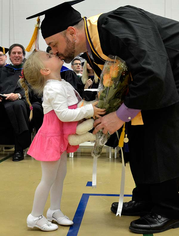 Graduating father giving his young child a kiss after receiving his diploma