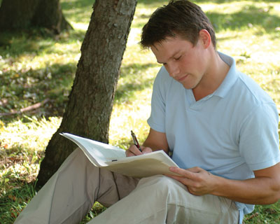 Student outside sitting by a tree doing homework