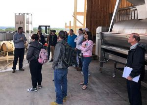 Students at the Buttonwood Grove Winery insde the barn where the wine is produced